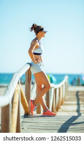 young woman jogger in sport clothes on the seashore looking into the distance. exercise improves not only your health but also your mood. workout on the seashore even more calming and stress relieving