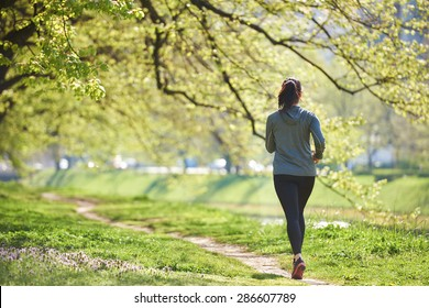 young woman jogging in city park at early morning
