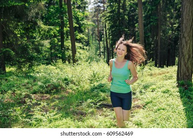 young woman jogging in a forest