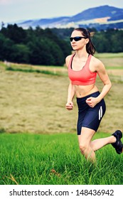 young woman jogging in front of cross country