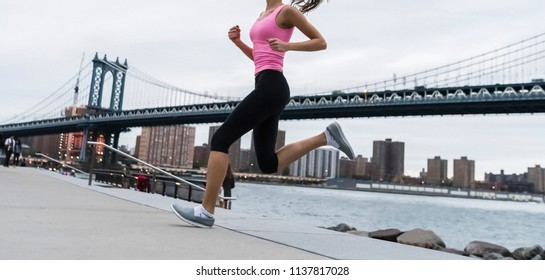 Young woman jogging in New York City at twilight