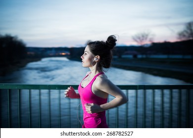 Young woman jogging at night in the city on the bridge cross the river. Girl running outdoors in a city park. Motion blurred image. Color toned image.