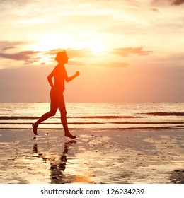 Young woman jogging on the beach at sunset