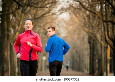 Young woman jogging in park, man running from opposite direction turns on her