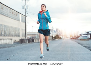 Young woman jogging in urban landscape at sunset