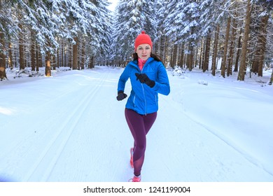 A young woman jogging in the wintry forest