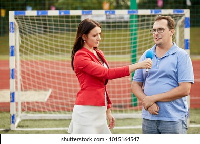 Young woman journalist interviews man near goal at stadium.