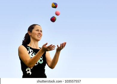 Young woman juggler is juggling balls.concept photo of flexibility, success, skill and control.