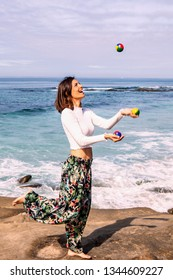 young woman juggling by the sea