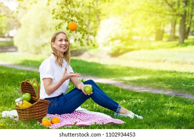 Young woman juggling fruits in park on picnic at sunny day, having fun and enjoying summertime