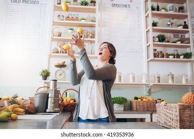 Young woman juggling with lemon at juice bar. Happy young female employee playing with fruits at juice bar.