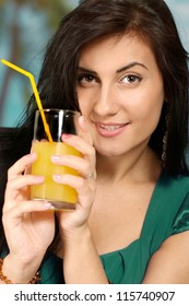 young woman with juice on a blue background