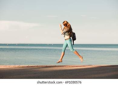 young woman is jump in front of sea