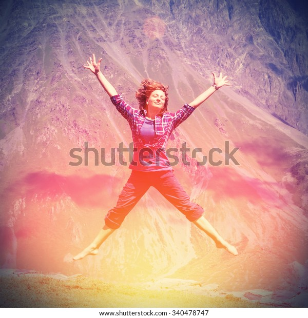 Young woman jumping with hands up against the mountain