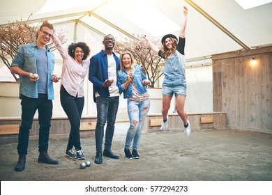 Young woman jumping with her arms up celebrating win in petanque game, her friends smiling, standing inside indoor petanque club