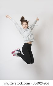 Young woman jumping high in happiness - studio shot.