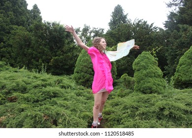 Young woman jumping with long wavy curly hair in pink dress on the green background of pure nature