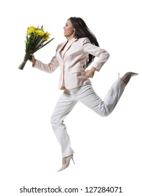 Young woman jumping in mid-air and holding a bouquet of flowers