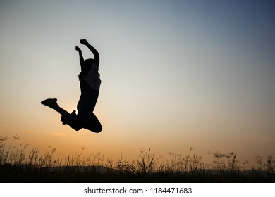 young woman jumping in the middle of a meadow in the light of the falling sun. In the evening
