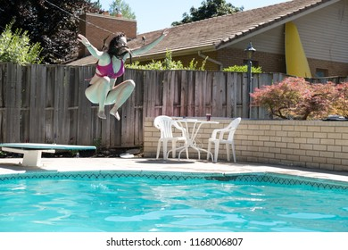 Young woman jumping off diving board into a backyard swimming pool arms up in the air legs tucked to her body caught in mid air. Girl in bikini jumps into outdoor swimming pool in the backyard.