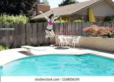 Young woman jumping off diving board into a backyard swimming pool arms up in the air legs tucked to her body smiling caught in mid air. Girl in bikini jumps into outdoor swimming pool in a backyard.
