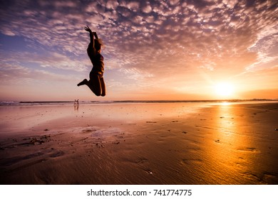 Young woman jumping on beach at sunset.