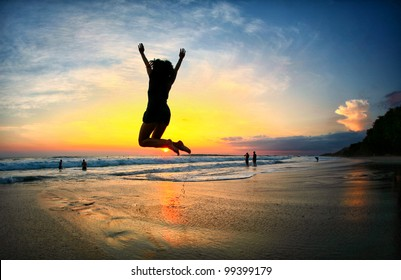Young Woman Jumping on Beach at sunset in Costa Rica