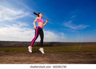 young woman jumping on blue sky background in countryside