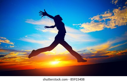 Young woman jumping on meadow on sunset sky background