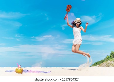 Young woman jumping on the tropical beach with happy on her vacation time. Summer travel.