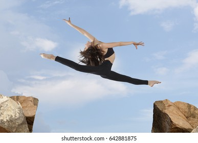 Young woman jumping over the gap at blue sky