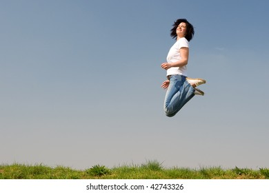 Young woman is jumping over a green