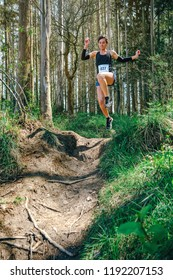 Young woman jumping participating in a trail race through the forest