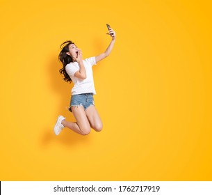 junge Frau springt beim Handy