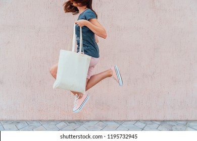 Young woman is jumping with white cotton bag in her hands.