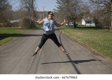A young woman jumps in the air in the street. Horizontal image.