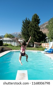 Young woman jumps off diving board into a backyard swimming pool. Woman entering the water after jumping off diving board. Girl in bikini mid air jumping into backyard swimming pool.