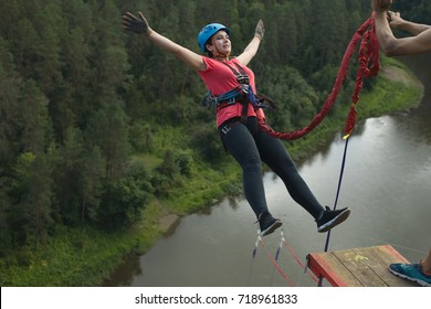 Young woman jumps on a rope from a great height. Ropejumping.