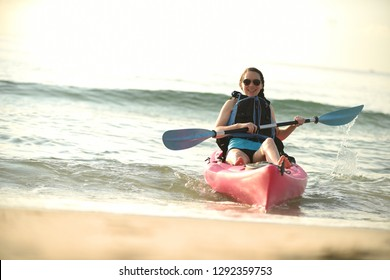 Young woman in kayak on beach in summer