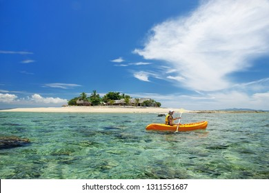 Young woman kayaking near South Sea Island, Mamanuca islands group, Fiji. This group consists of about 20 islands.