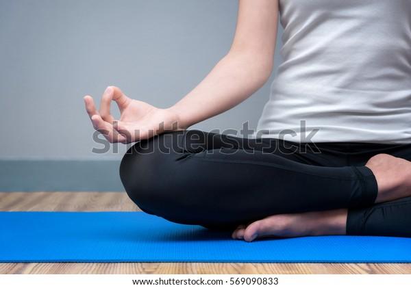 若い女性は、心の平和を探るためにヨガの練習をしながら、冷静に瞑想を続けます。ヨガや瞑想は健康に良い利点がある。