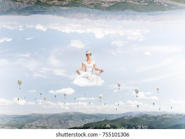 Young woman keeping eyes closed and looking concentrated while meditating on cloud among flying aerostats and between two nature worlds.