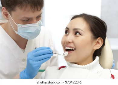 Young woman keeping her mouth open while dentist examining it. Dental photo series