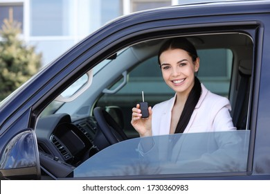 Young woman with key sitting in car outdoors. Buying new auto
