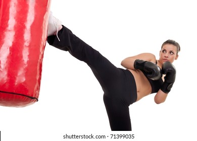 young woman kick a punching bag- isolated on white