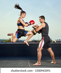 Young woman kickbox fighter training with her coach on the roof above the city