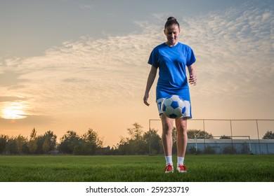 young woman kicking soccer ball