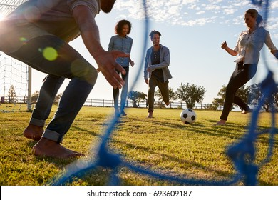 Young woman kicks football while playing with friends