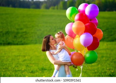 Young woman with kid in white dress with colorful balloons outdoors. Mom kissing daughter. Happy family enjoying fresh summer air.