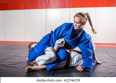 A young woman in a kimono makes a painful reception. Judo, jujitsu. Tatami, gym